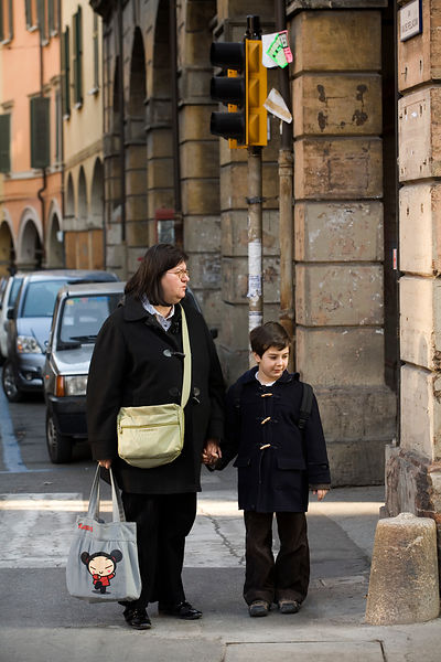 Italy - Bologna - A mother and son wait to cross the road