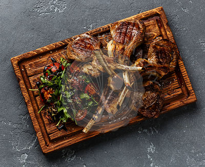 Grilled lamb ribs with tomatoes and arugula salad on cutting board on dark background