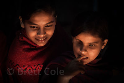 Two girls stay warm at a fire at night in Sovabazar, Kolkata, India. One of the girls is missing an eye.