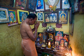 India - Swamimalai - The family priest offers prayers at the family shrine in the Stapathy house