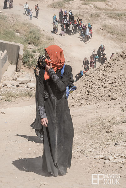 A woman shields her mouth and nose from the dust as she walks away from her home, displaced by the battle for Mosul. Mushaari...