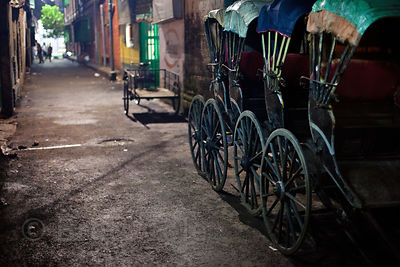 Rickshaws parked in a shady alley in Bowbazar, Kolkata, India.