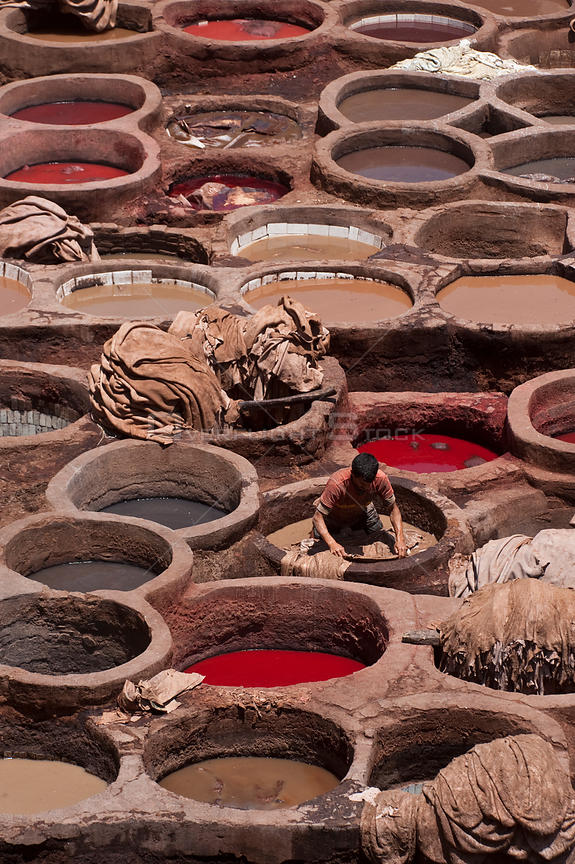 People working in the dyeing vats at the traditional leather tanneries, Fes, Morocco, June 2009
