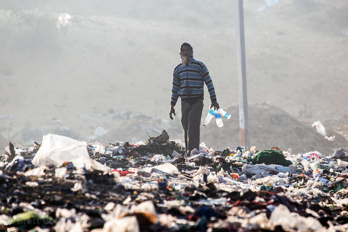 A man collects plastic drinkin water bottles to be recycled in the Pushkar municipal dumping ground (landfill), Pushkar, Raja...