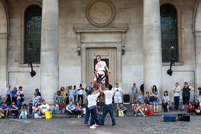 UK - London - A street performer is helped onto a unicycle by members of the audience in from of St Paul's Church, Covent Gar...