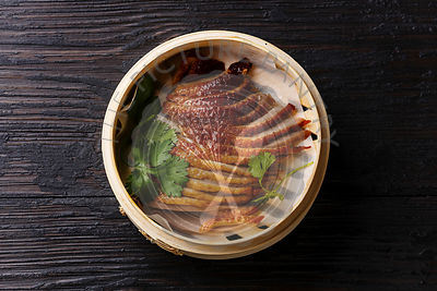 Peking Duck in bamboo steamer with fresh cilantro on black burned wooden background