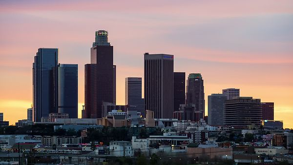 Medium Shot: L.A. High-Rises Towering Light Rail During A Sunset (Day To Night)