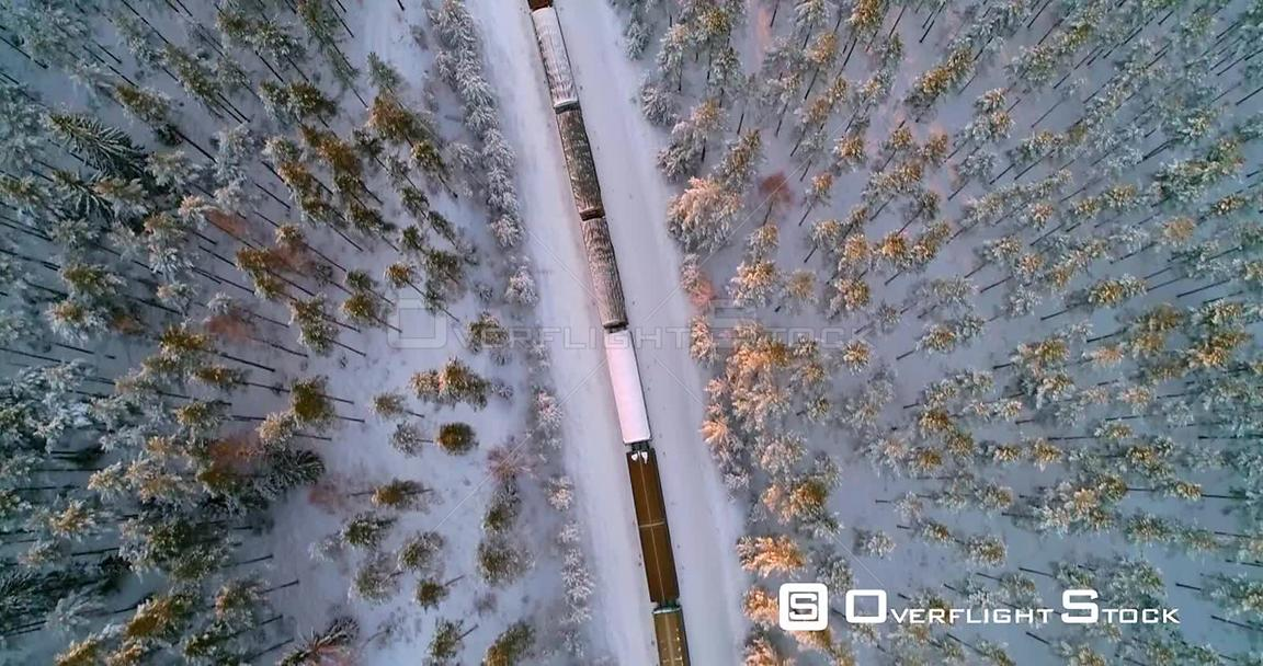 Train in Finnish Winter, Aerial, Top Down, Drone Shot, Following a Cargo Locomotive, in a Snowy Forest, in the Scandinavian C...