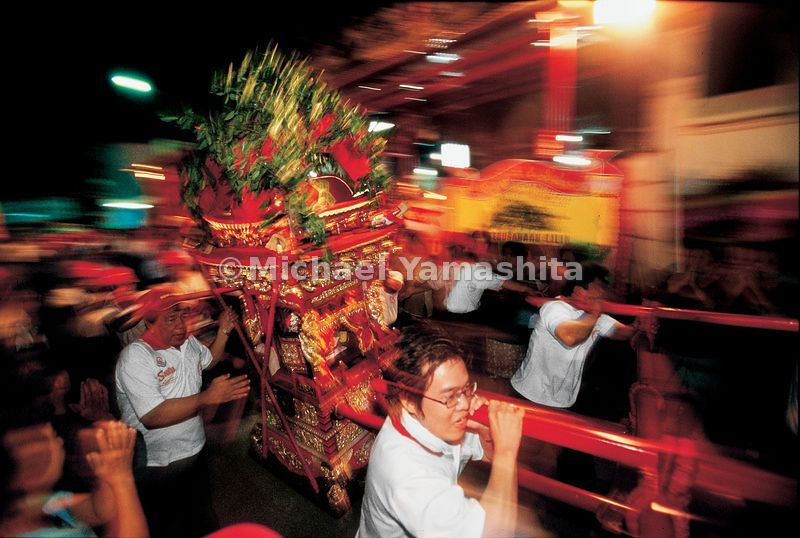 An image of Zheng He is paraded through the streets of Semarang inside a portable shrine, mimicking the movement of a ship ov...