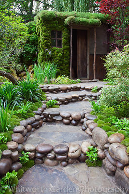 A path edged with decorative rounded pebbles and moss mounds with Pachysandra terminalis leading to a garden room in the Japa...