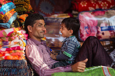 Father and son share a moment in a textiles shop in Pushkar, Rajasthan, India