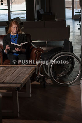 Young student reading a textbook in a cafe lounge chair