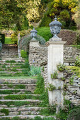 Stone steps link terracing on the steep site, framed with clipped rosemary bushes. Iford Manor, Bradford-on-Avon, Wiltshire