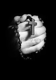 Hands holding onto rosary beads and cross while praying.