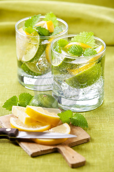 Cold fresh lemonade with lemon and lime on green background