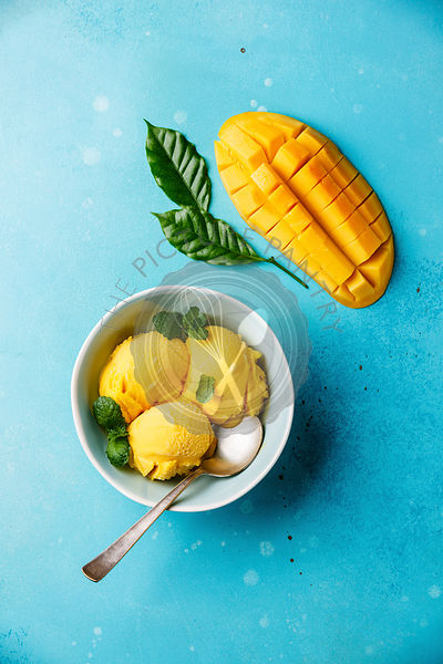 Mango ice cream sorbet with mint leaves and Fresh mango on blue background