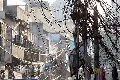 A tangle of electrical wires lines a street in Chandni Chowk, Delhi, India