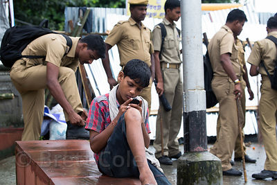 A boy taps on a phone while police officers chat behind him, Babughat, Kolkata, India