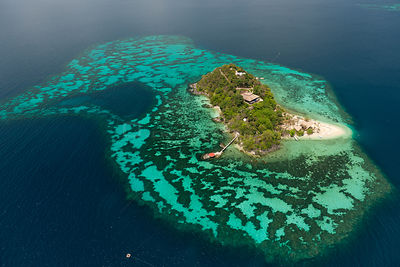 Aerial view of private tropical island surrounded by a white sandy beach and coral reefs, note helipad on end of pier, Palawa...