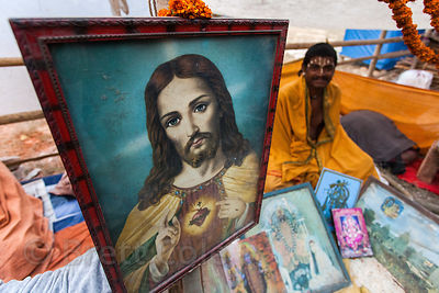 A pilgrim sits next to a painting of Jesus at a staging area in Kolkata, India for pilgrims going to the Gangasagar Mela on S...