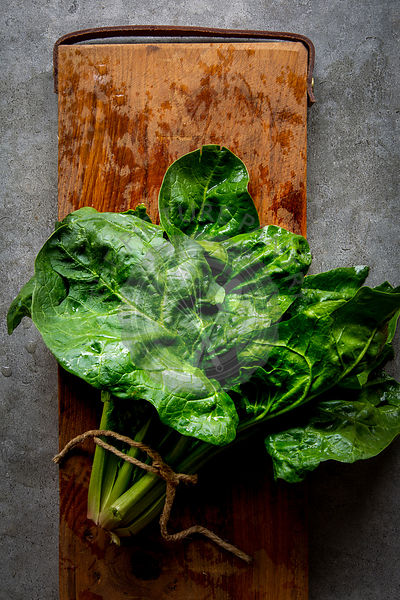 Bundle of fresh spinach on wooden board over grey concrete background