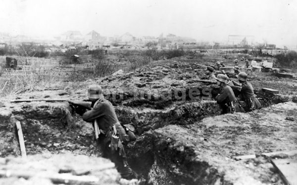 German soldiers fire from trench during WWI