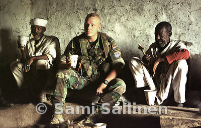 A Dutch peacekeeper drinks suwa, the Eritrean homemade beer, with Orthodox Christian priests..Photo by Sami Sallinen