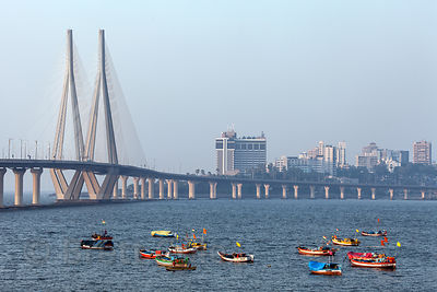 Fishing boats in Mahim Bay and the Bandra-Worli Sealink bridge, Mumbai, India.
