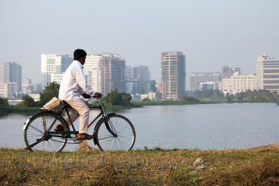 A man rides a bike past shallow lakes in the East Kolkata Wetlands, Kolkata, India. In the distance is the planned satellite ...