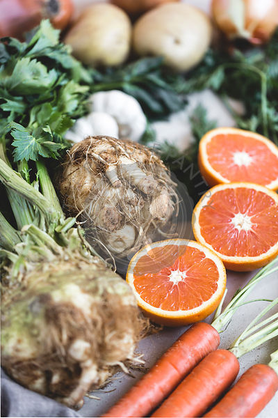 celery root, sliced oranges, carrots, and onions are photographed from the front view.