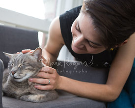 Young Woman Petting Grey Cat on Chair