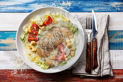 Caesar salad with chicken breast on wooden background