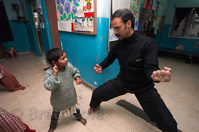 A girl at a shelter for homeless or otherwise at-risk girls in Kolkata, India takes a karate class to build confidence and assertiveness. She had just arrived at the shelter this day.