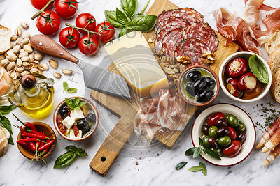 Italian snacks food with Ham, Sliced bread Ciabatta, Olives, Parmesan cheese, Grissini bread sticks, Feta cheese with dried t...