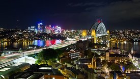 Bird's Eye: Lovely Wide Shot Of Sydney's Skyline Lit Up At Night With Traffic & The Bridge In The Foreground