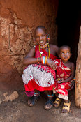 Maasai woman with child sitting at her hut in the manyatta, Kenya