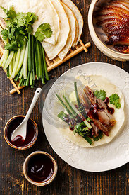 Peking Duck served with fresh cucumber, green onions, cilantro and roasted wheaten chinese pancakes with sauce Hoysin on wood...