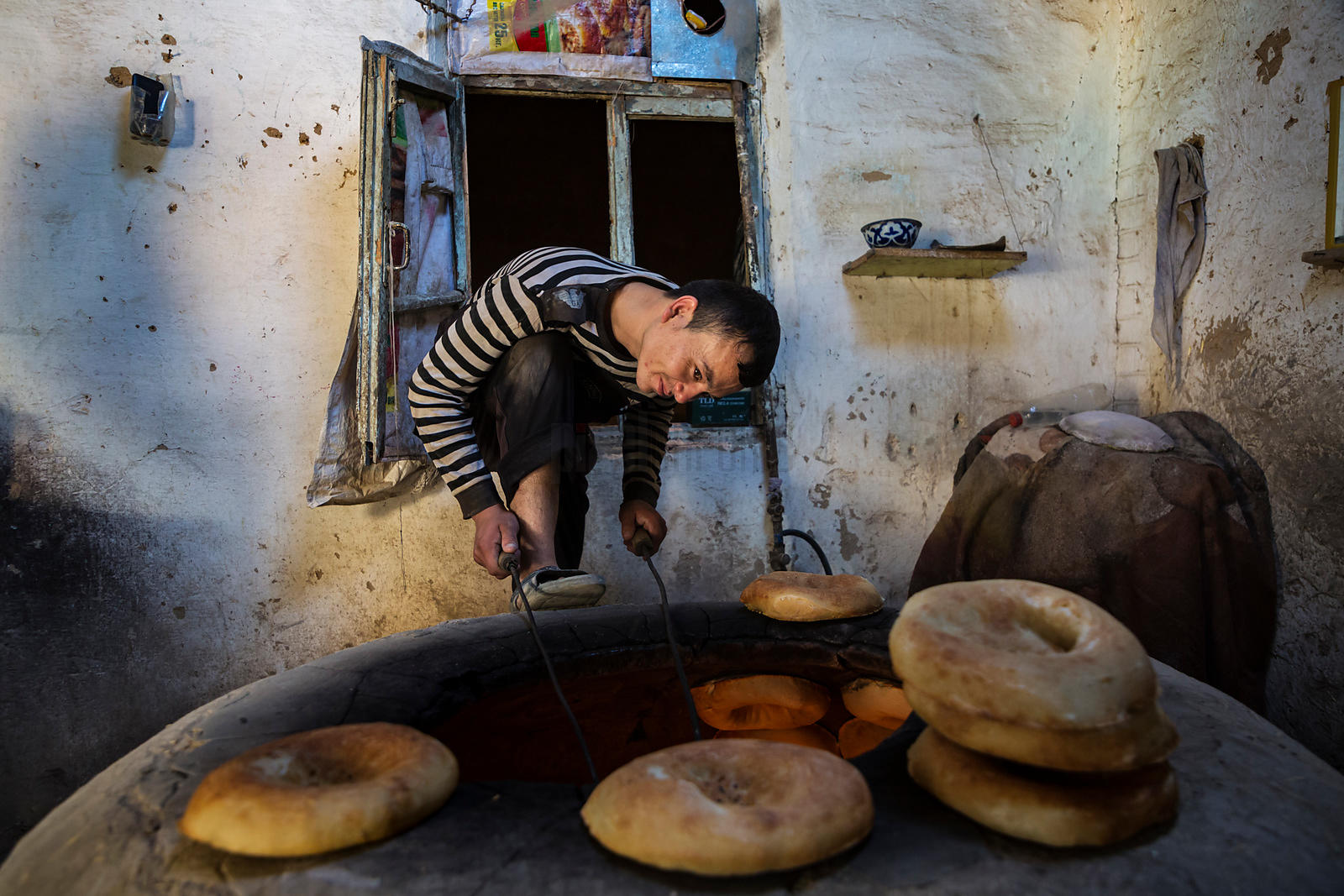 A Baker Prepares to Remove a Loaf of Freshly Cooked Bread from the Oven