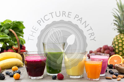 Five glasses of fresh smoothies (in all different colors) are photographed from the front view in a white backdrop.