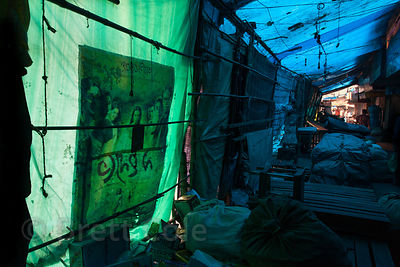 A backlit Bollywood poster on a street full of yet-to-open market stalls, Newmarket, Kolkata, India.