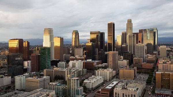 Bird's Eye: L.A. Skyline Under A Dramatic Cloud Deck & Metallic Sunset (Day To Night)