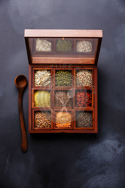 Superfoods and cereals selection in wooden box: oat, mung, quinoa, bulgur, flax seed, goji berry, polba, lentil and chia on dark background