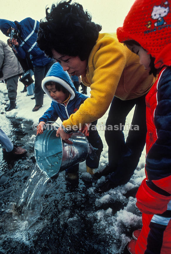 A youngster starts salmon fry on their way to the sea in Sapporo's Salmon Baby Festival, an event that reintroduced the fish ...