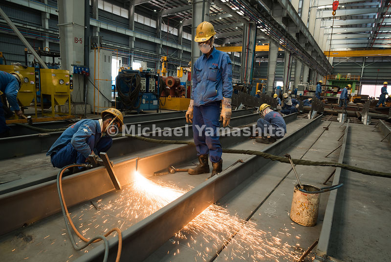 In a workshop, steel fitting works for marine and offshore engineering projects are carried out by workers.