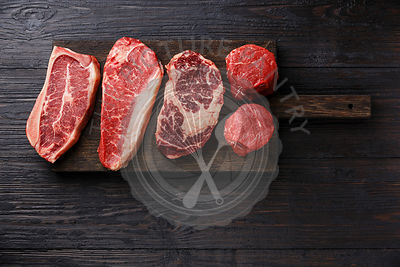 Variety of Raw Black Angus Prime meat steaks Blade on bone, Striploin, Rib eye, Tenderloin fillet mignon on wooden board copy...