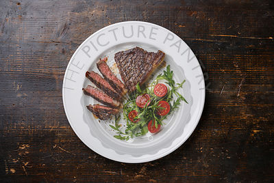 Sliced medium rare grilled Beef steak Striploin and salad with tomatoes and arugula on white plate on dark wooden background