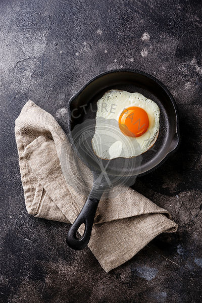 Fried egg on iron pan on dark background copy space