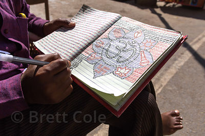 A man draws and writes poetry in a notebook, Pushkar, Rajasthan, India