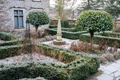 Courtyard garden featuring beds enclosed by clipped box hedges, standard bay trees and a central stone obelisk.