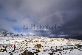 A rainbow over a hiker on a snow covered Beinn Eighe in the Scottish Highlands, Scotland, UK.